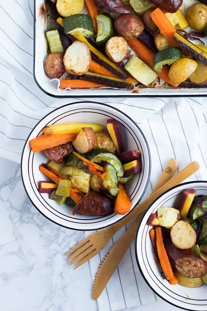 An overhead shot of sausages and veggies in two bowls and a sheet pan