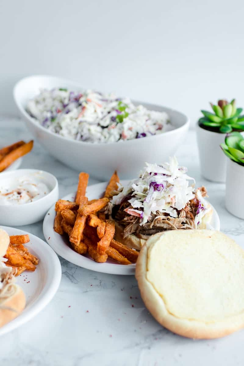 Blue Slaw on bbq sandwich with sweet potato fries, dish of slaw in the background, with two succulents