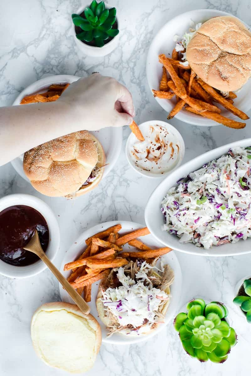 hand dipping sweet potato fry into sauce, pulled pork sandwiches on plates with coleslaw