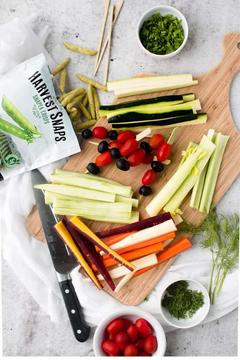 Vegetable sticks and harvest snaps on a wooden board