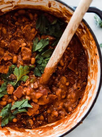 baked beans in dutch oven with wooden spoon