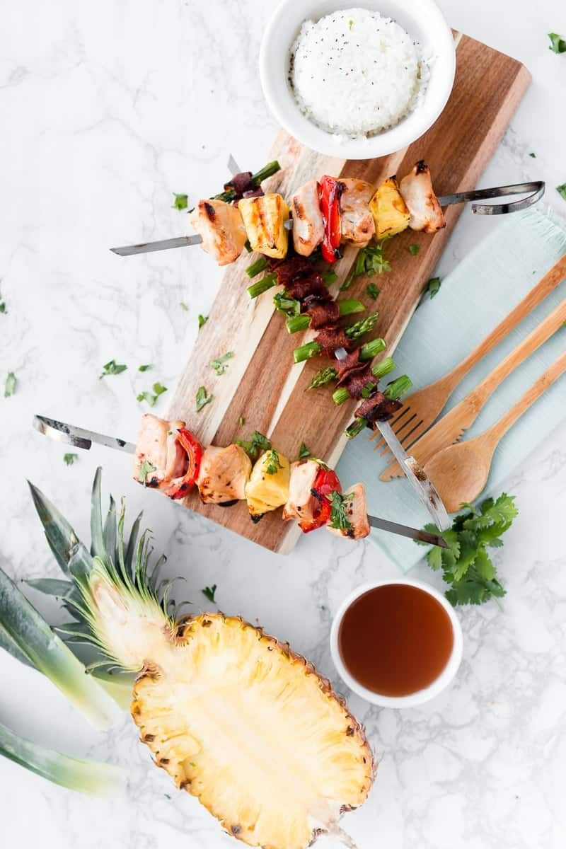Three Disneyland Bengal BBQ Copycat kabobs on a wooden board with a pineapple and dipping sauce