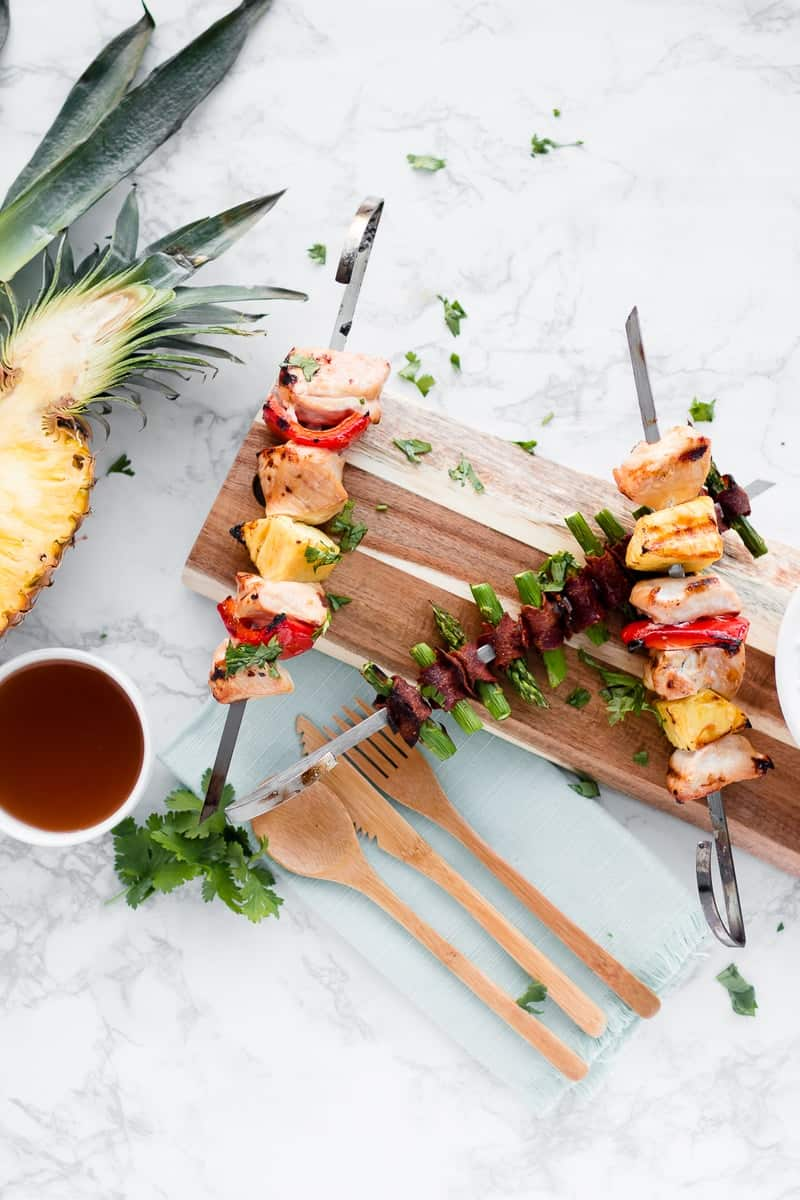 Two Disneyland Bengal BBQ Copycat kabobs on a wooden board with a sliced pineapple