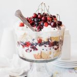 trifle glass bowl with layered trifle and berries piled on top. Spoon placed in scooping out.