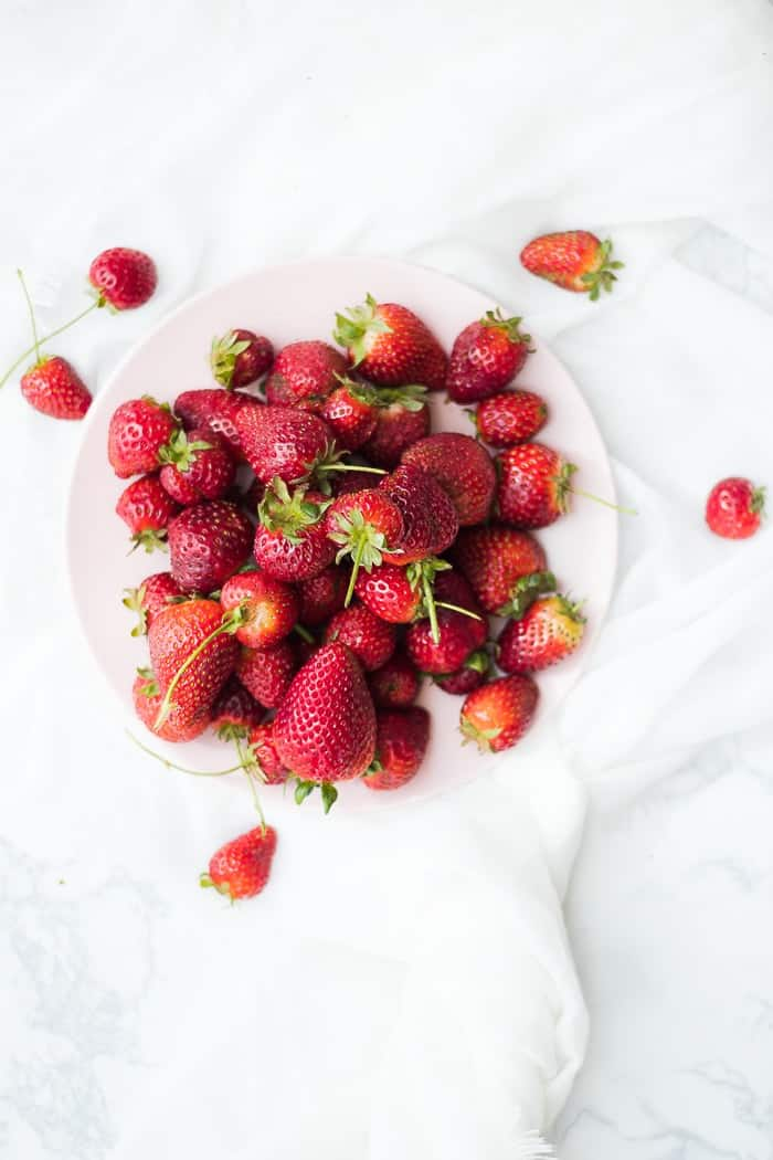 A pile of strawberries on a plate to make homemade jam