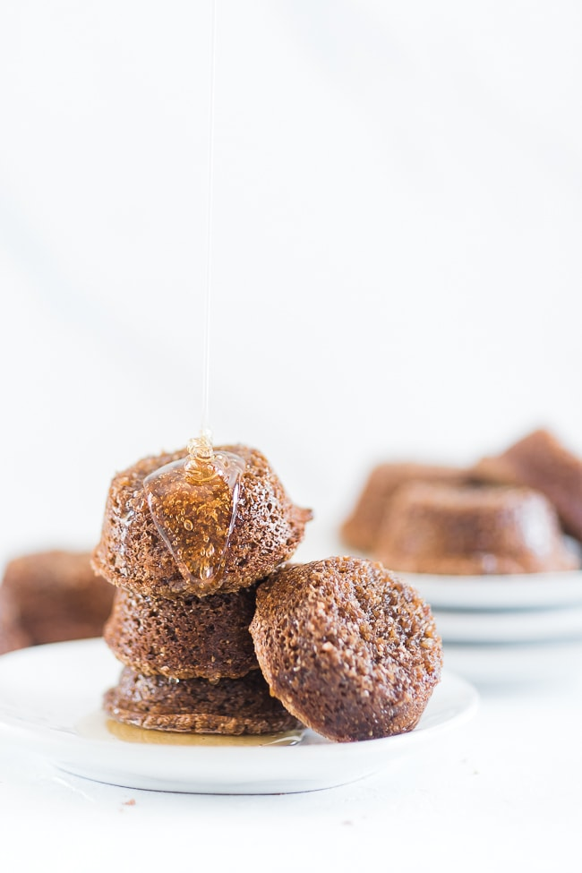 Molasses bran muffins stacked on a white plate.