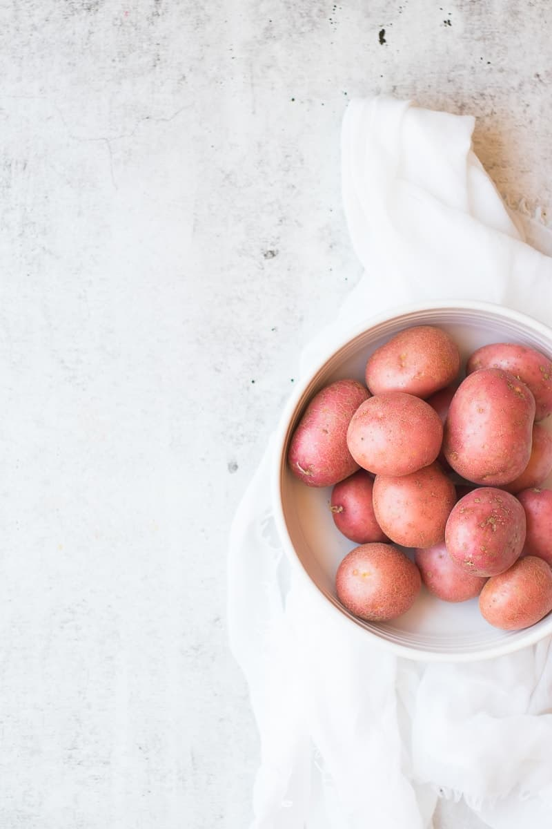 An overhead shot of red potatoes in a white bowl with a white dishcloth