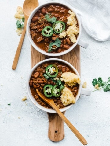 Best Chili Con Carne in white bowls atop a brown cutting board.