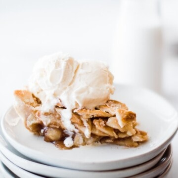 slice of apple pie with ice cream on top on a stack of plates