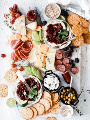 cheeseboard with cheese, cranberry salsa, apples and crackers