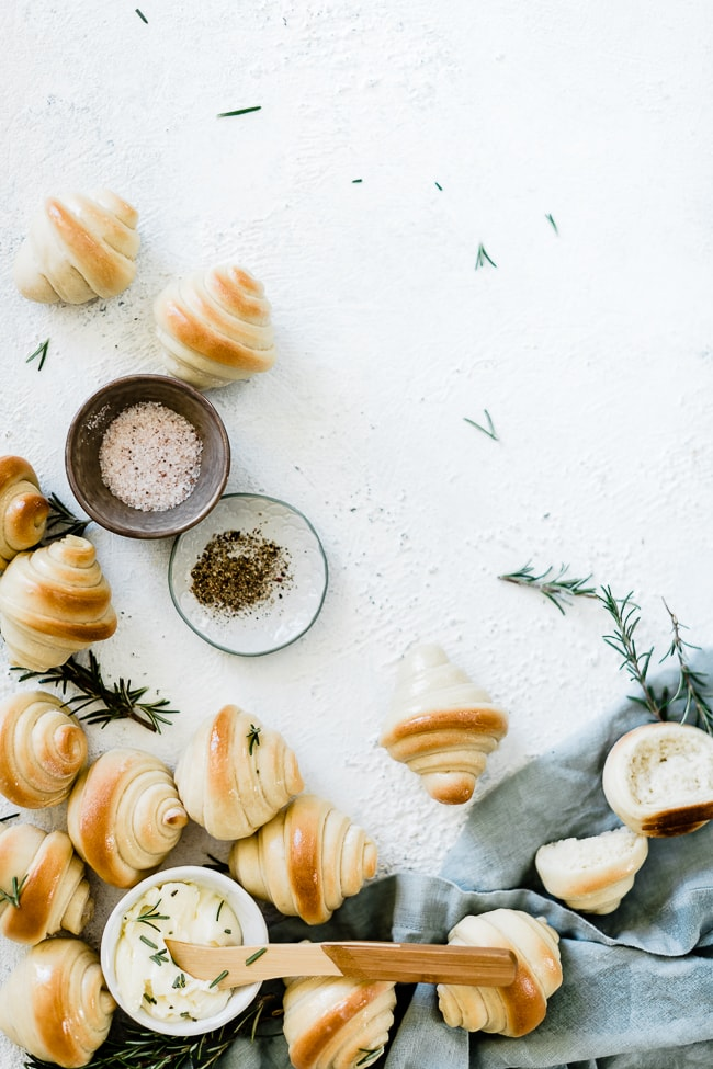 Homemade crescent rolls arranged on a countertop with rosemary and salt and pepper.