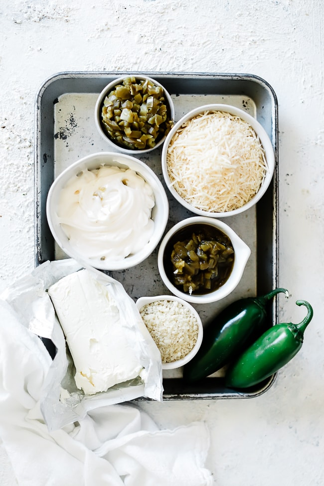 Ingredients needed for jalapeno popper dip in a baking tray: cream cheese, mayo, parmesan, green chilies, jalapeno, panic.