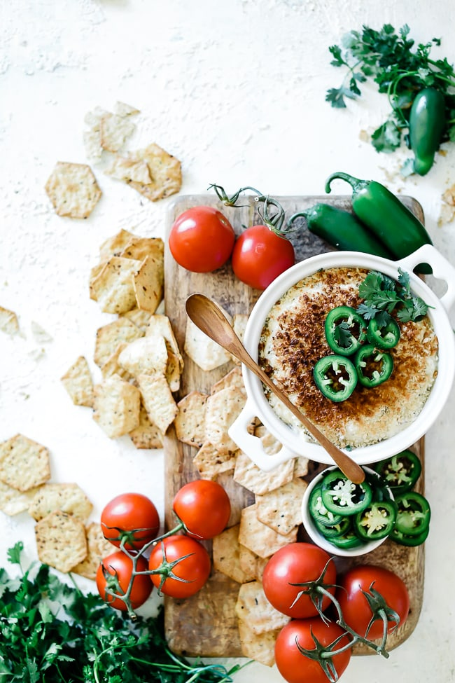 Jalapeno popper dip recipe in a round white baking dish. The dish is placed atop a wooden board and is surrounded by crackers and fresh tomatoes. The dip is garnished with jalapeños.