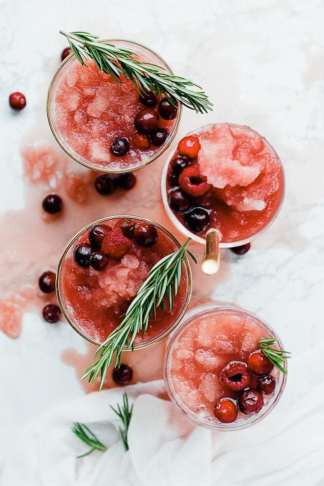A birds eye view of cranberry pineapple slush punch in glasses. Garnished with rosemary and fresh cranberries.