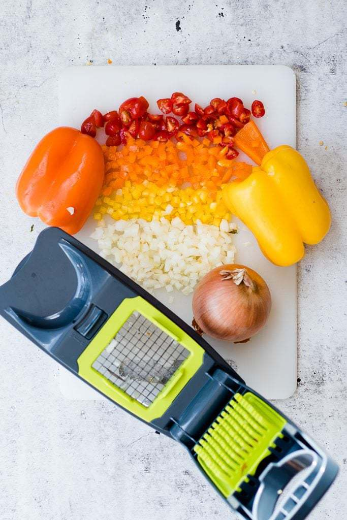 Chicken Roll-Up ingredients with a vegetable chopper diced up on a chopping board