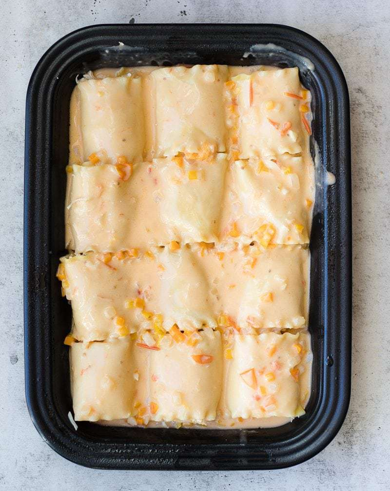 Chicken Roll-Ups ready to bake in a black dish