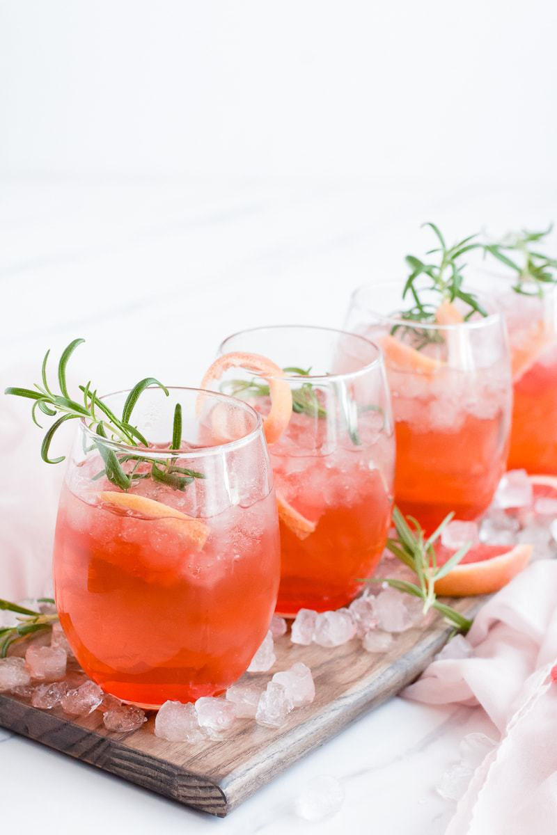 Ruby Red Grapefruit Sparkler cocktails topped with rosemary sprigs