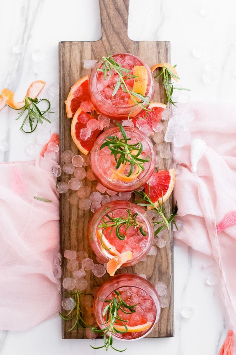 Ruby Red Grapefruit Sparkler cocktails on a wooden board with ice