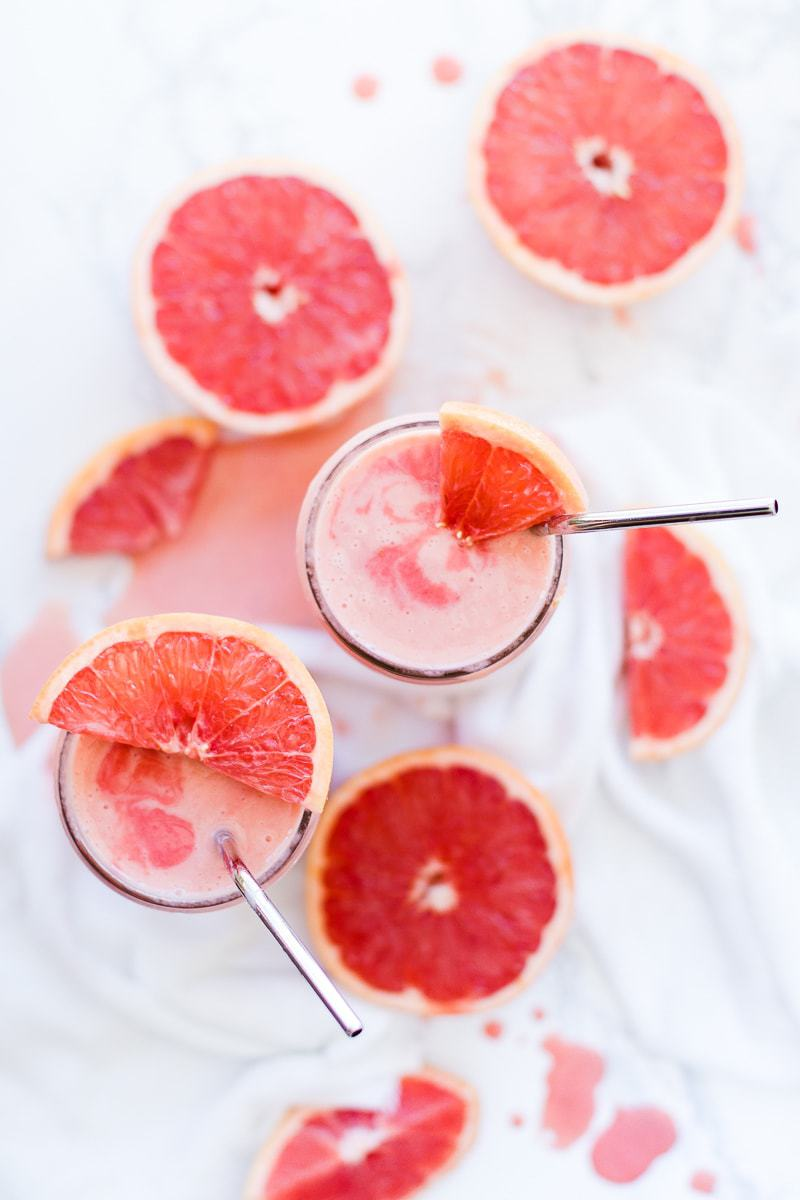 Two glasses of Strawberry Grapefruit Smoothie on a white surface with slices of grapefruit