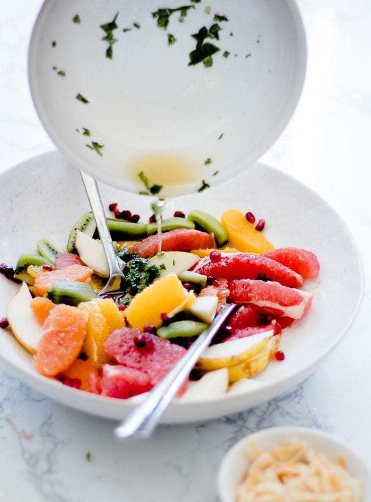 pouring dressing over tropical fruit salad