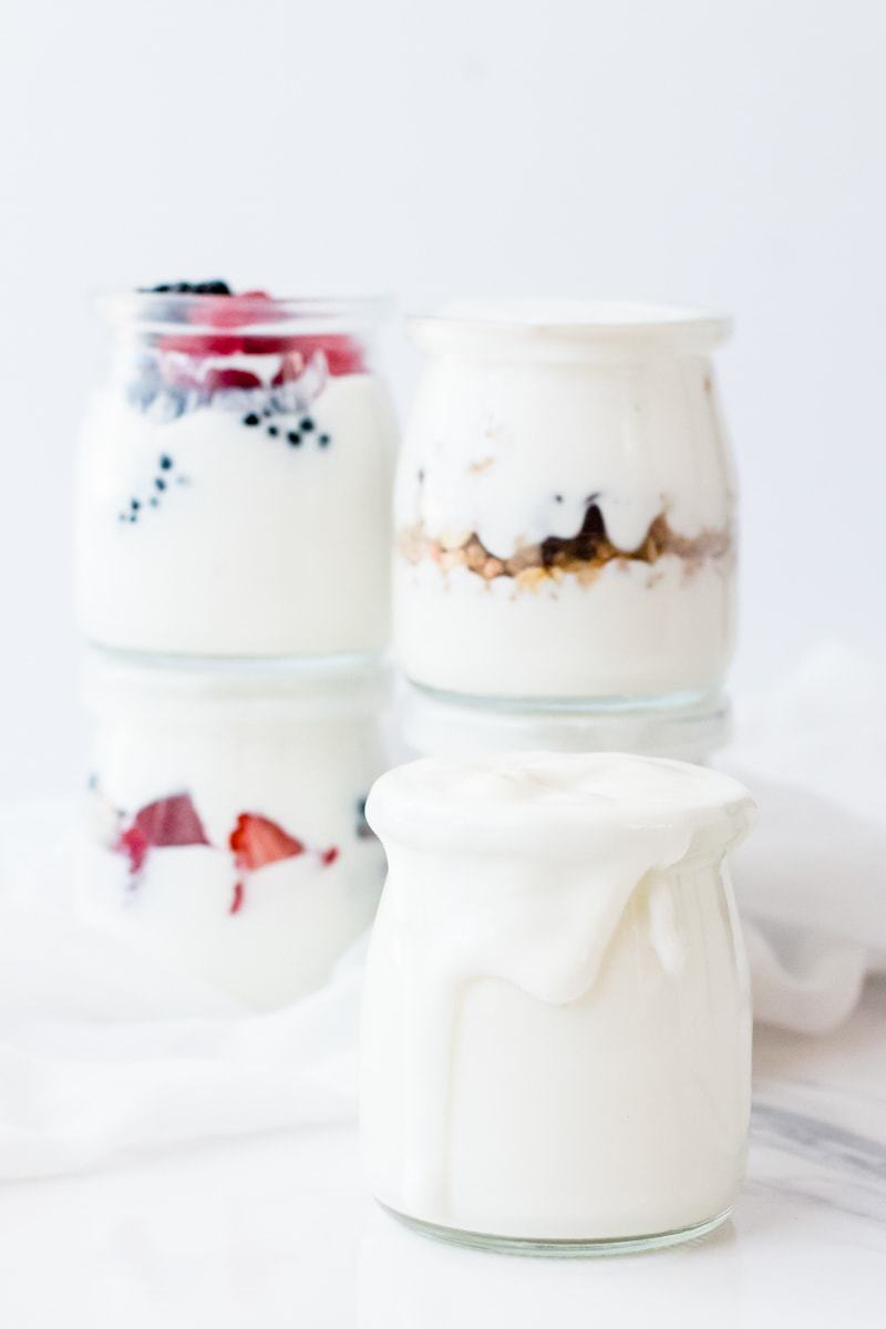 instant pot cold start yogurt in mason jars with yogurt overflowing down the sides
