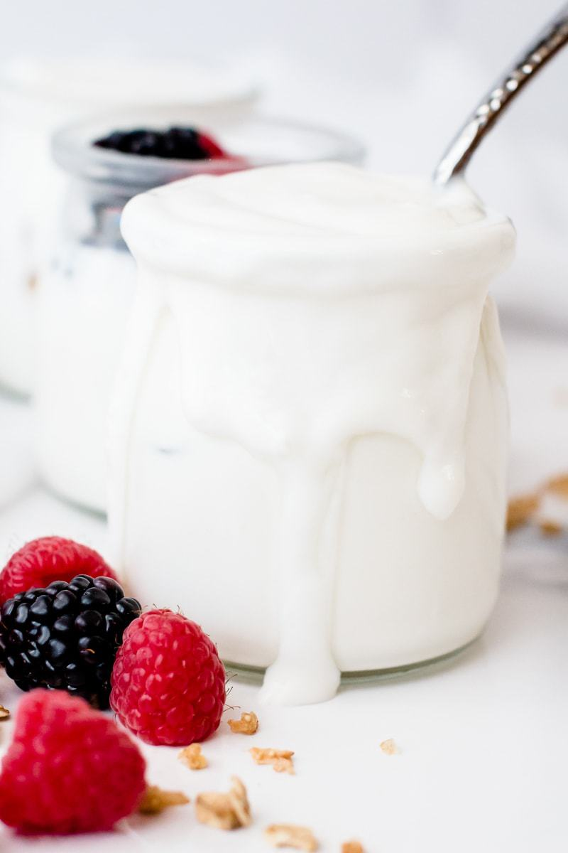 Instant Pot Cold Start Yogurt in a mason jar with fresh fruit at the side
