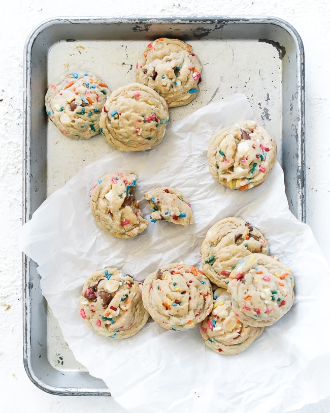 Birthday cake cookies scattered on a baking sheet.