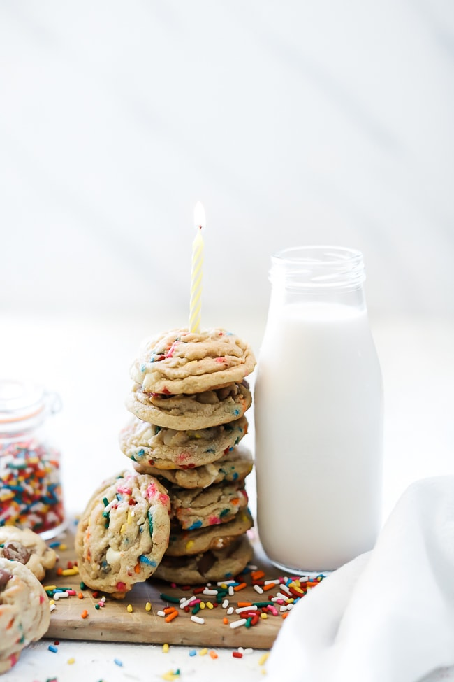 Birthday cake cookies stacked next to a bottle of milk. The Cookes have a candle stuck in them.