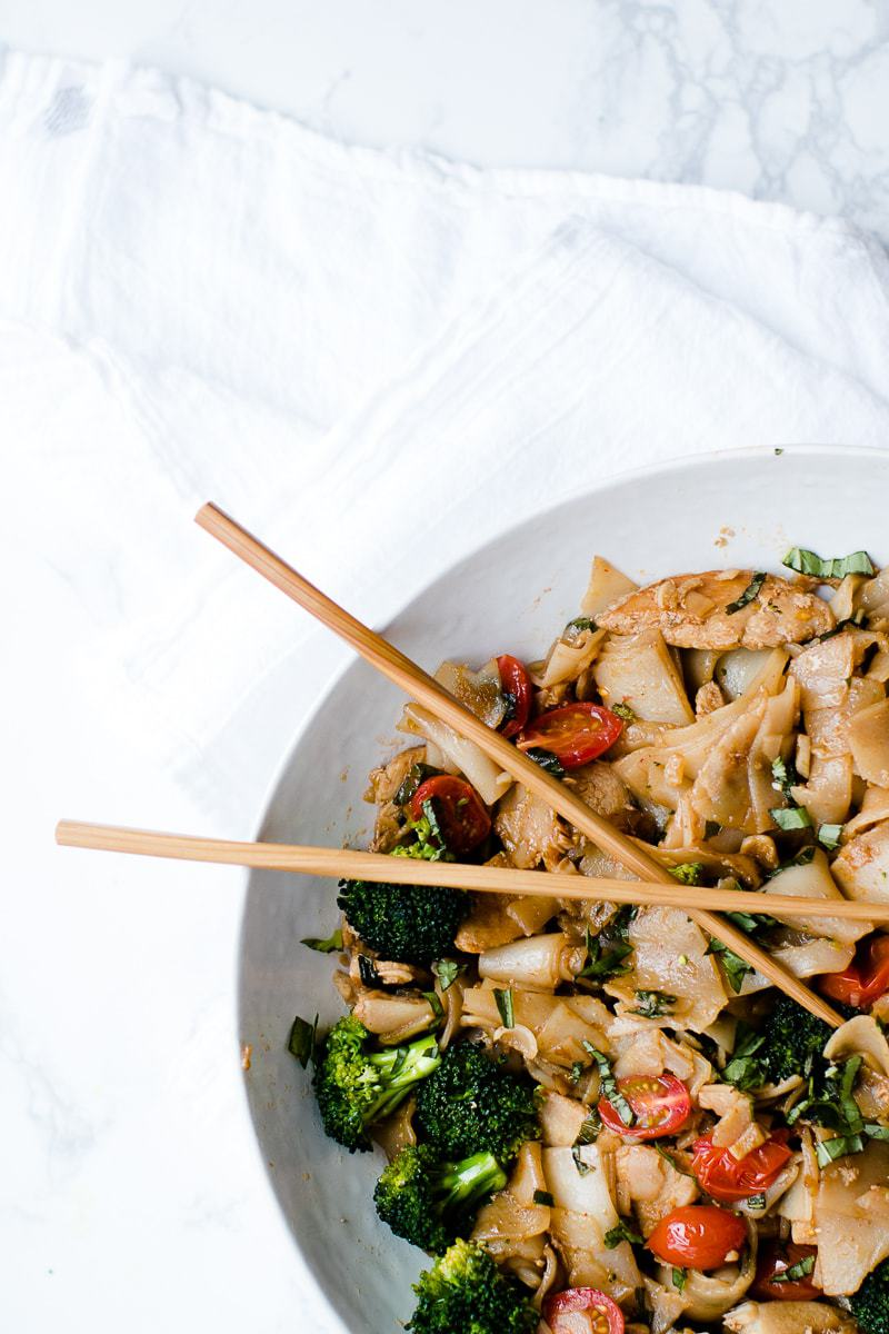 thai drunken noodles with chopsticks in a white bowl on a marble surface
