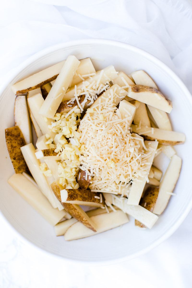 Raw garlic fries in a bowl topped with parmesan and garlic ready to be baked