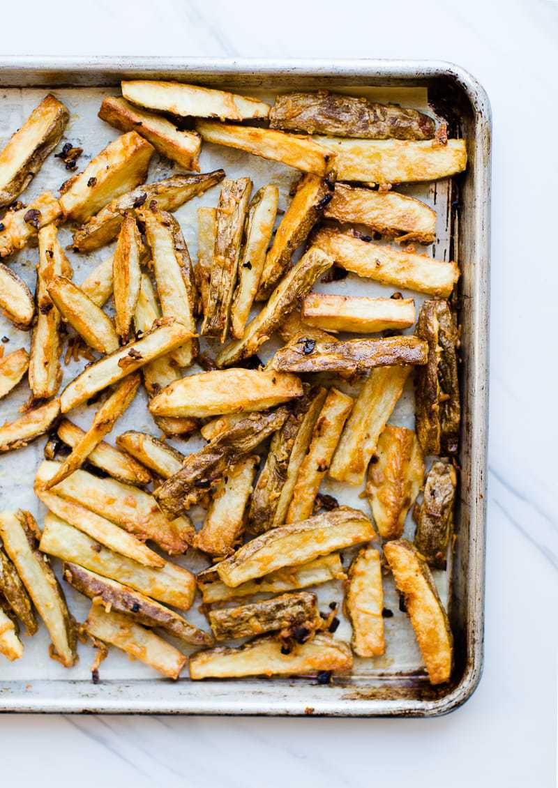 A close up of garlic parmesan fries on a sheet pan