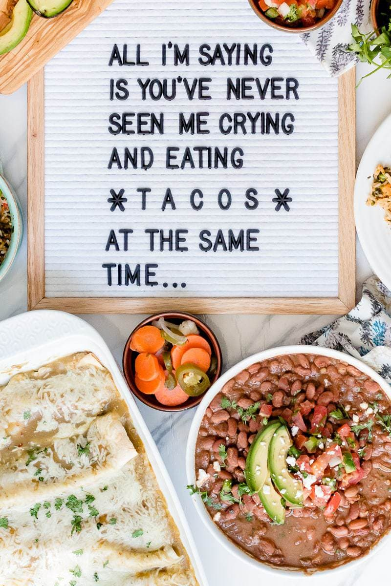 "enchiladas in baking dish, bowls of beans and chiles. letter board that reads,, ""All I'm saying is you've never seen me crying and eating tacos at the same time..."""