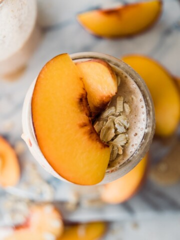 cup of smoothie with peaches and oats on top