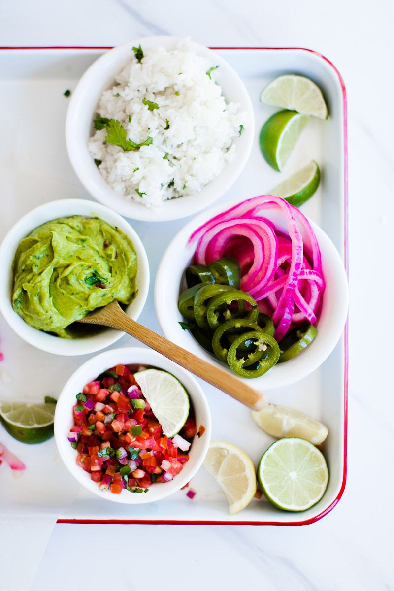 Red pickled onion and other ingredients to make tacos on a white tray