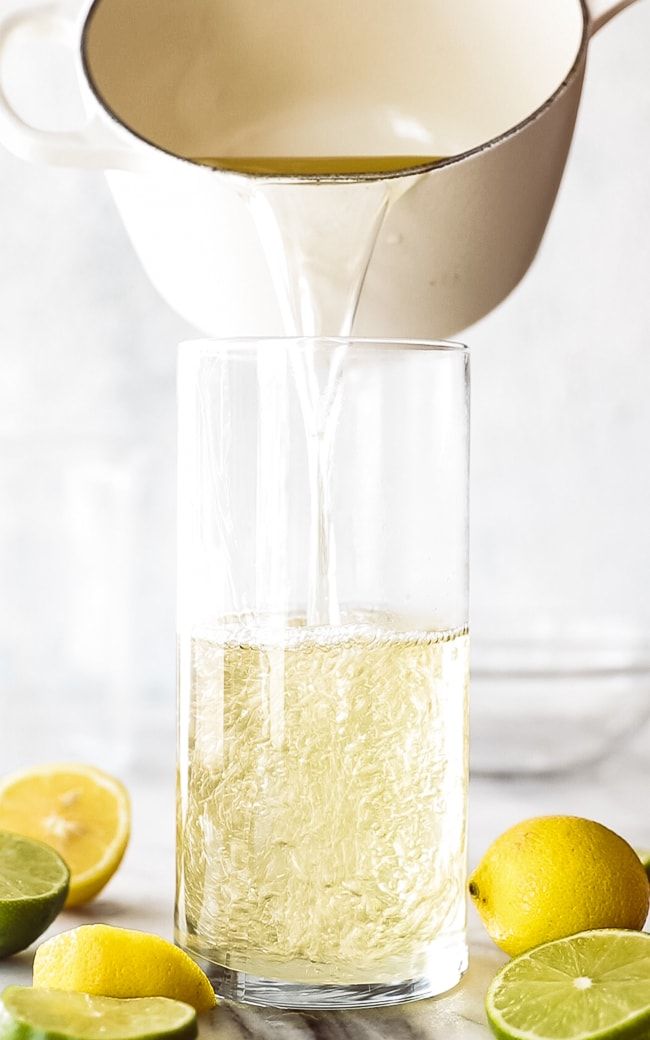 white pan pouring simple syrup into a glass container