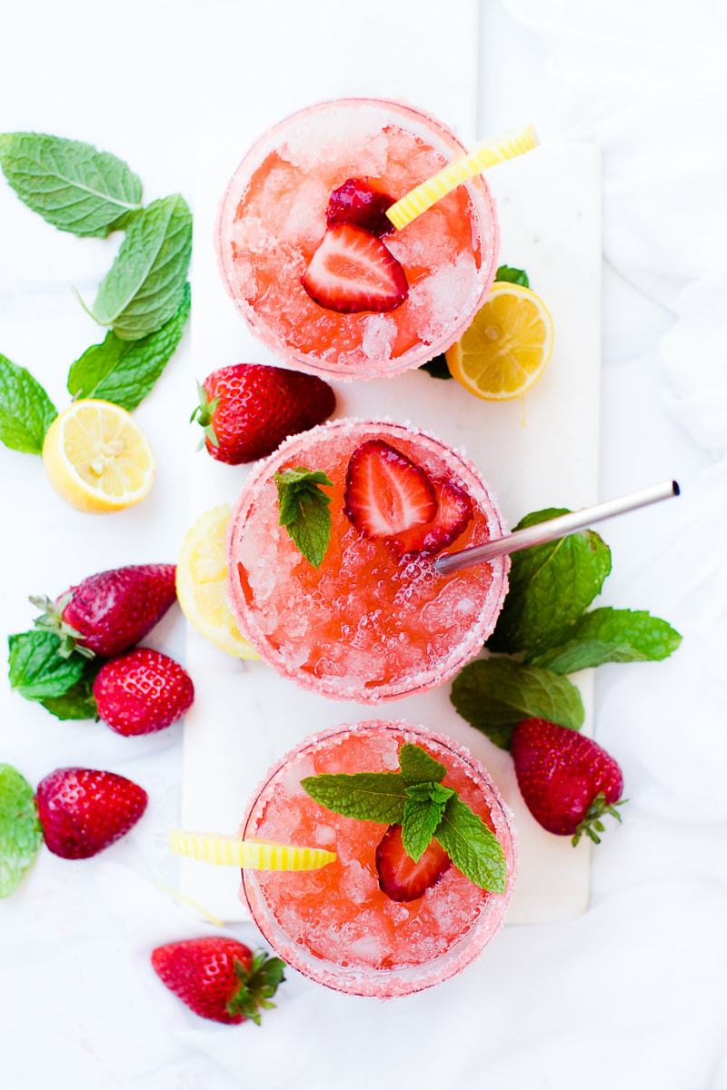 An overhead shot of 3 glasses of homemade strawberry lemonade topped with strawberries and mint leaves