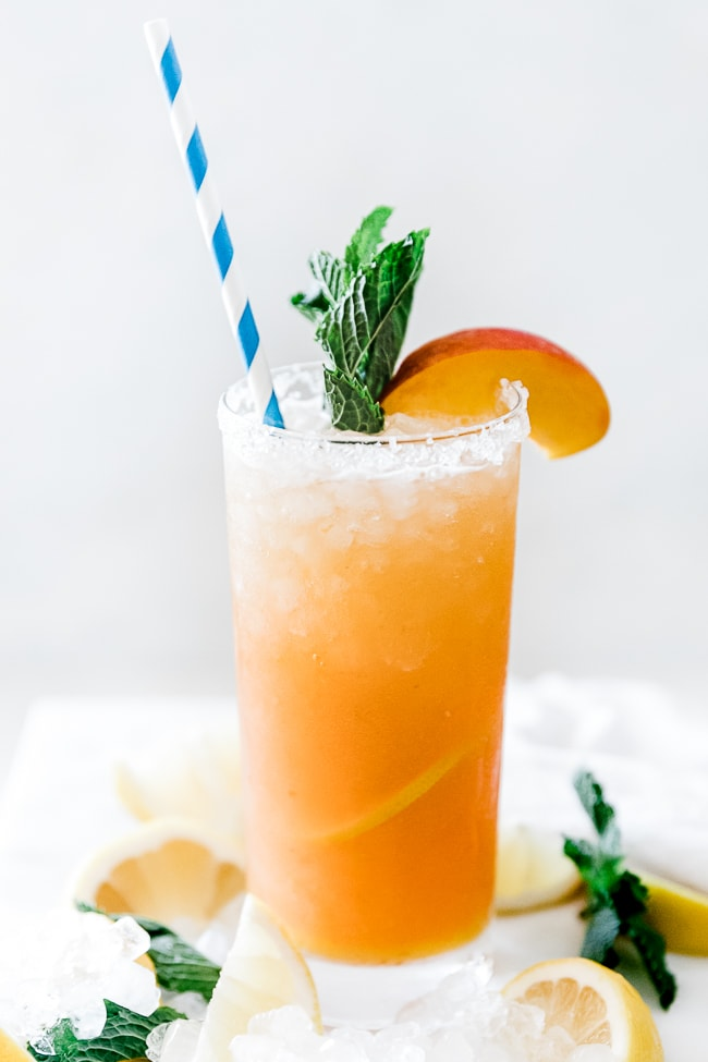 A closeup of a glass of peach lemonade. The glass is garnished with mint and peach slices.