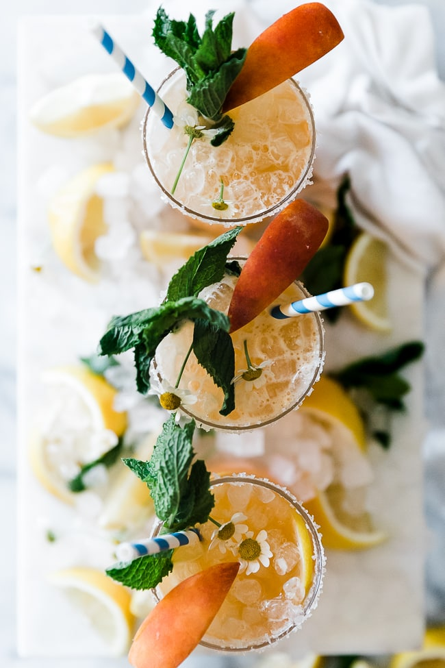 An overhead shot of three glasses of peach lemonade placed in a row.