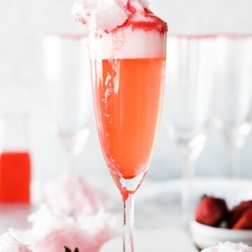 single champaign glass with sparkling strawberry lemonade and cotton candy as garnish on top
