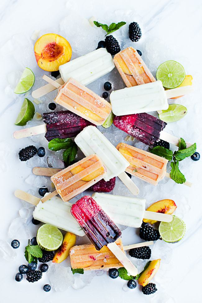Different flavored fruit popsicles on a marble surface with ice and fresh fruit