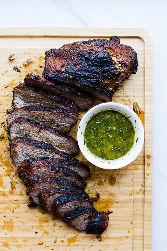 smoked tri-tip on cutting board with chimichurri saiuce