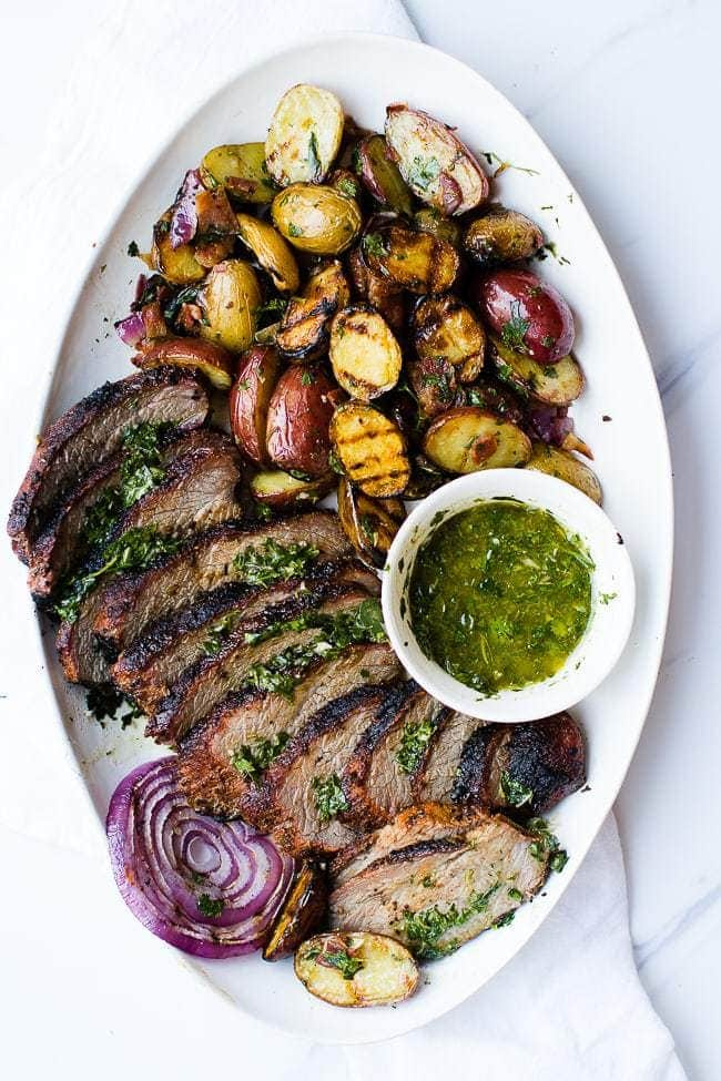 grilled tri-tip and grilled potato salad on platter with dip in cup