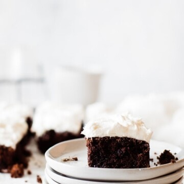 frosted chocolate zucchini cake on a stack of white plates