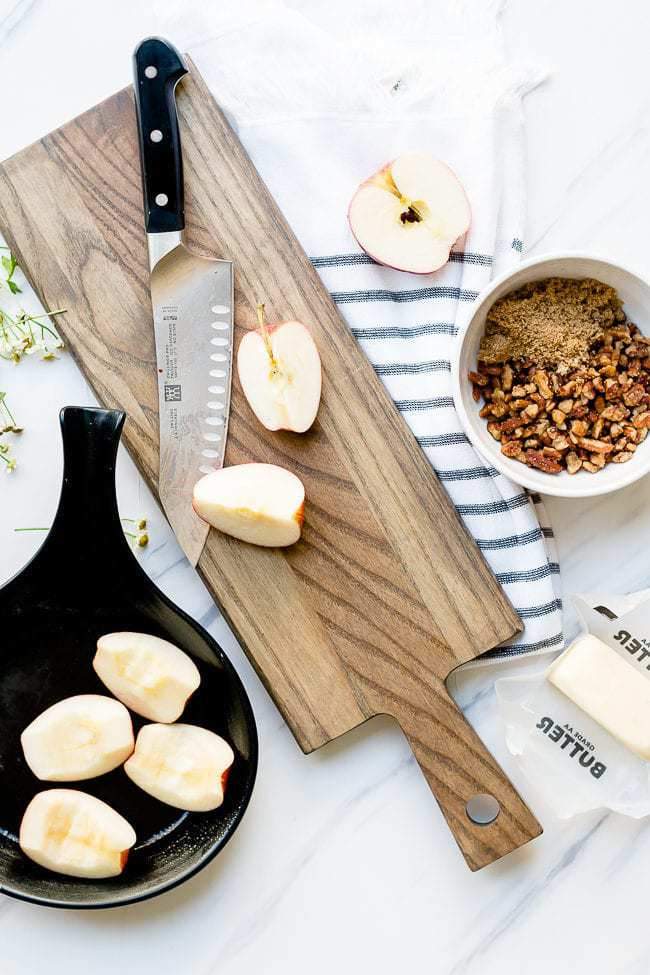 Baked apple salad prep. Sliced apples on a wooden cutting board.