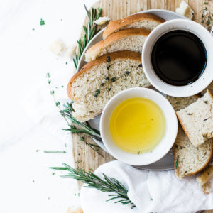 sliced bread on cutting board with balsamic vinegar and olive oil