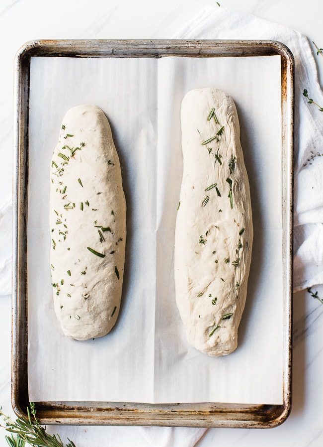 two loves of dough rolled out with herbs on top