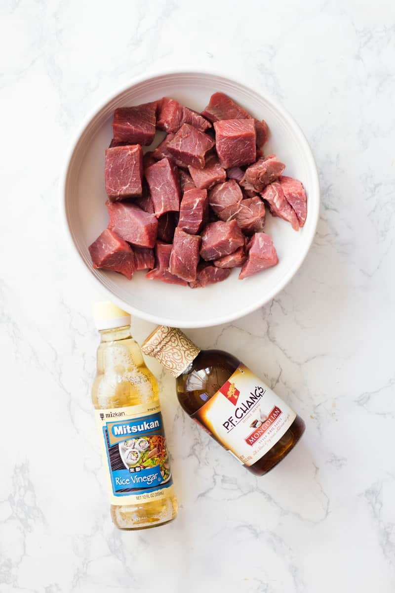 raw beef in bowl with marinade sauce bottles