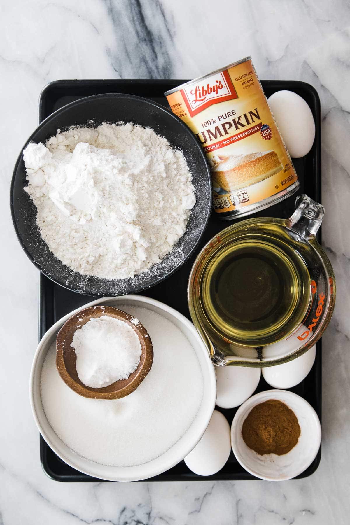 tray of ingredients; flour, pumpkin, oil, eggs, sugar, flour, baking soda and powder