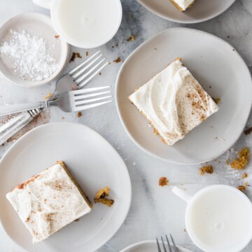 four plates of pumpkin cake with frosting