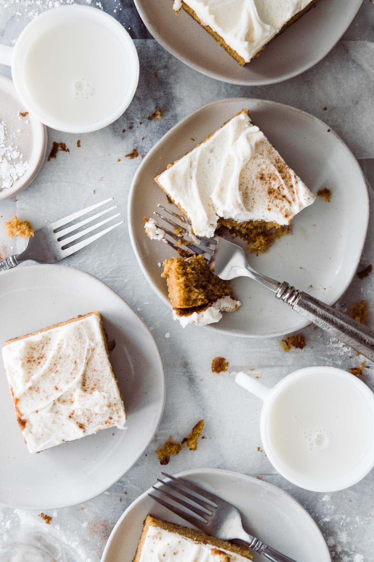 four slices of pumpkin cake on small plates. One slice with a fork taking a bite out.